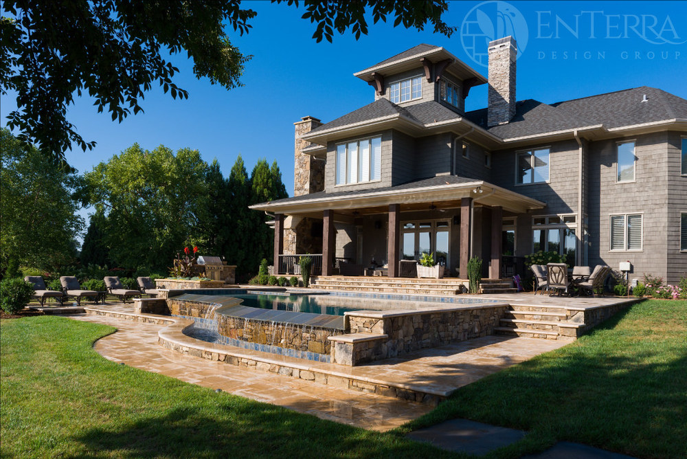 """The design includes an """"in-pool"""" spa,an outdoor kitchen, multi-tiered travertine pool deck, custom bocce court, & backyard landscape."""