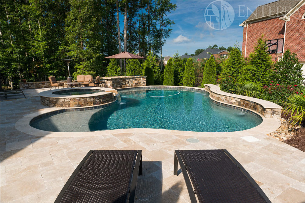 This design features a spa, tanning ledge, raised beam with water spillways, & pool-side bar.