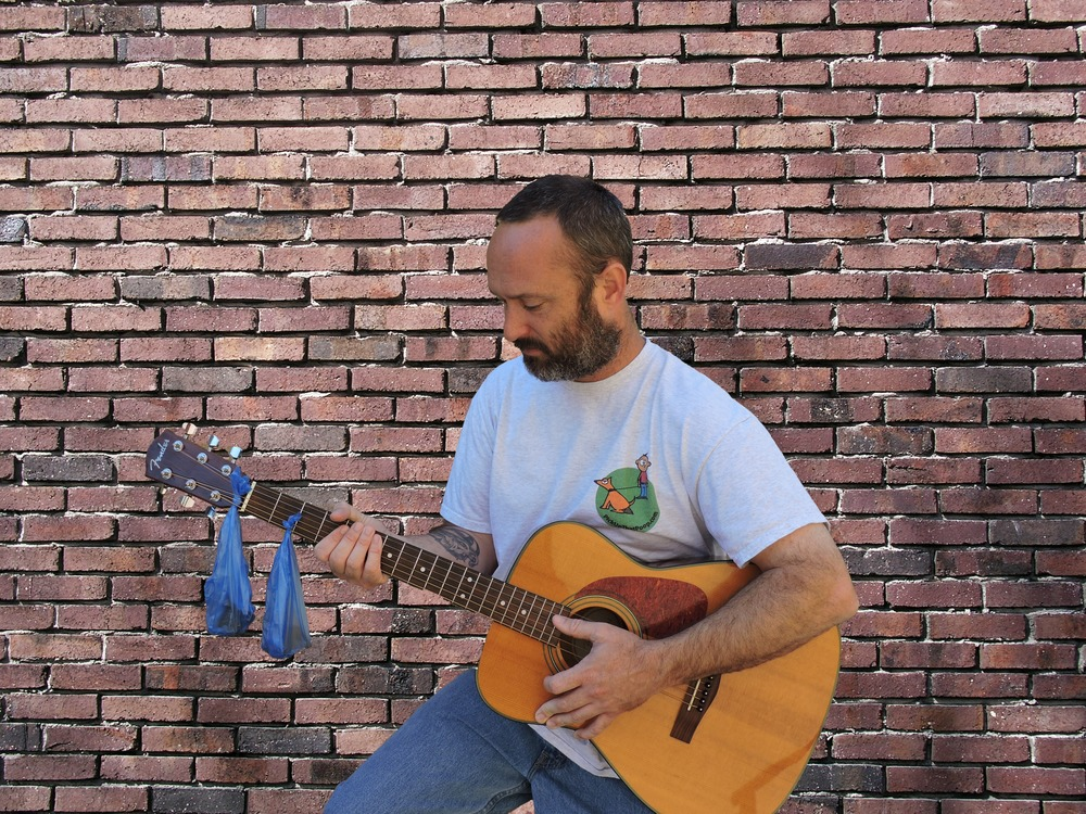 Chad Logan of Poop Bag Music playing his guitar and singing about dog poop.