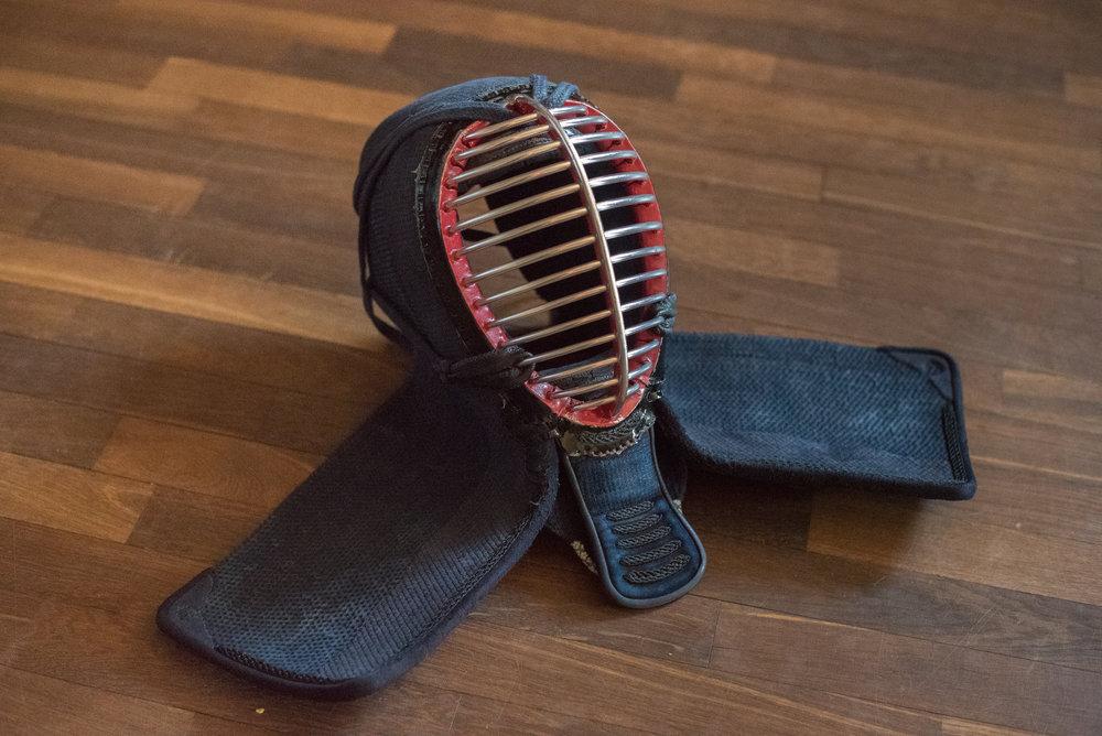 """""""Men"""" er det japanske ord for den maske, der beskytter ansigtet med et metalgitter (mengane) og struben med fotun. Den bindes fast på hovedet med snore (men-himo)."""