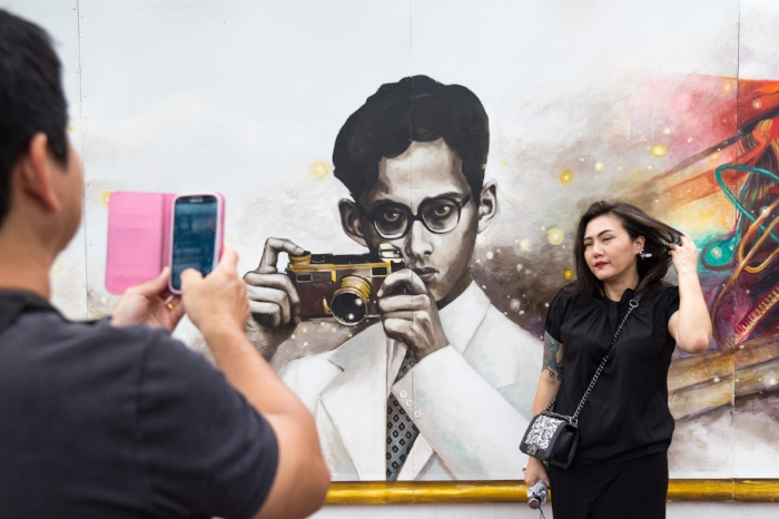 Mourner takes picture with painting a of King Bhumibol Adulyadej