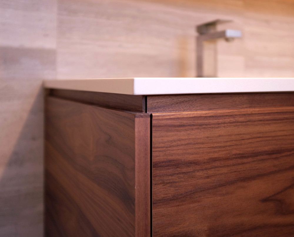 Corner detail showing the shadow reveal turning the corner on the custom walnut vanity.