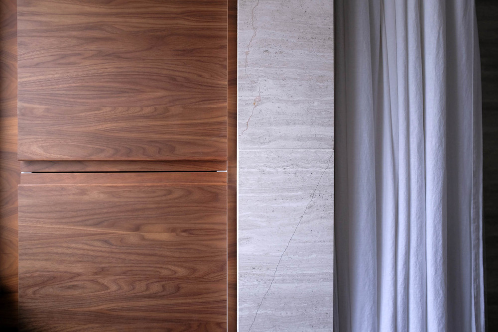 A detail of the material palette: walnut, limestone and linen.