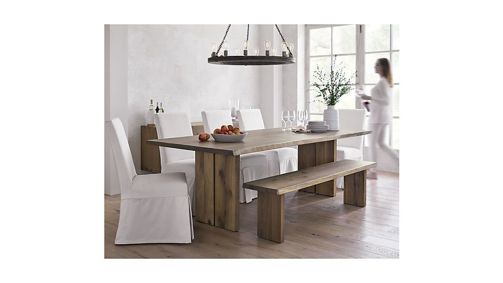 The  Dakota  dining table and bench really stood out to me due to its minimal design and the live-edge detailing. The white oak wood is a fantastic middle tone color and the two pieces together look refined and organic. I would put some sheep skins on the bench to make it more comfortable, but otherwise love the white slip cover chairs and vase that are styled with this collection.