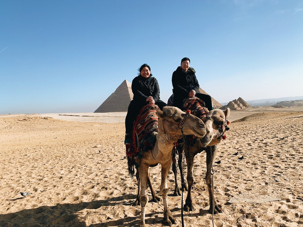 My husband and I on camels in Giza, Egypt with the Great Pyramids.