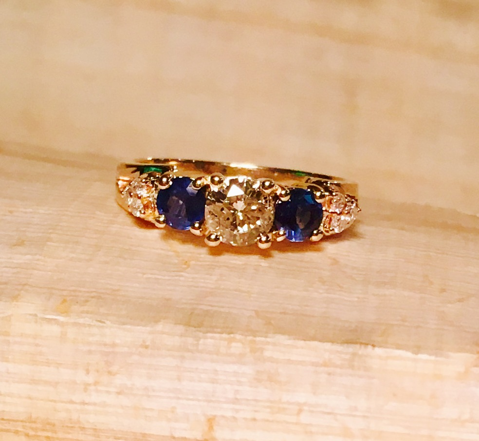 This was a ring given to mom when she delivered her son, she then gave to son to give as an engagement ring, but the center had a pearl which we removed and added a diamond,  and we supplied 2 ceylon sapphires on each side of the center diamond and made this new ring!