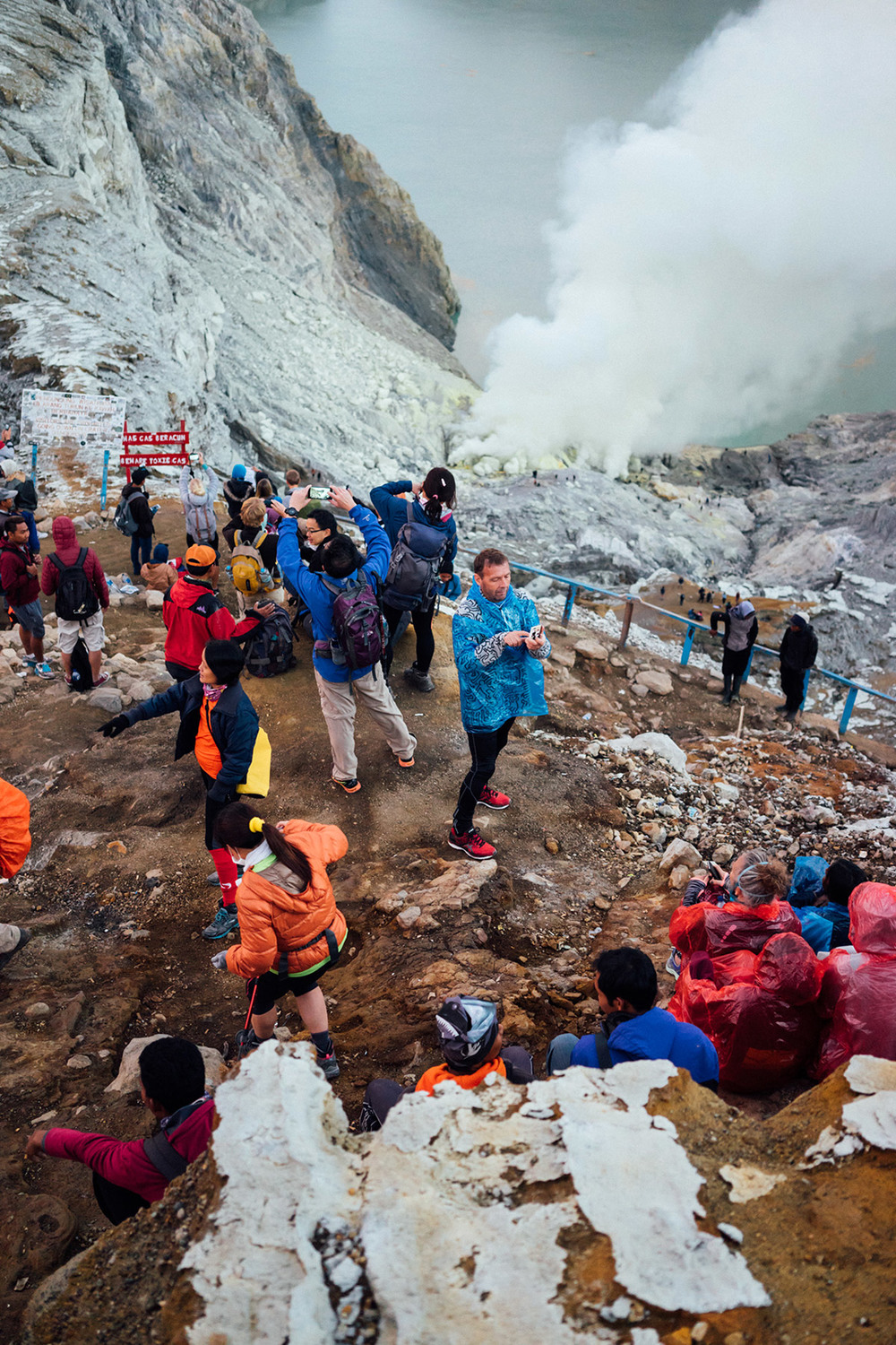 A colorful mix of local guides, miners, and hikers at the ridge of the Kawah Ijen crater, with its sulfuric gas and acidic lake below.