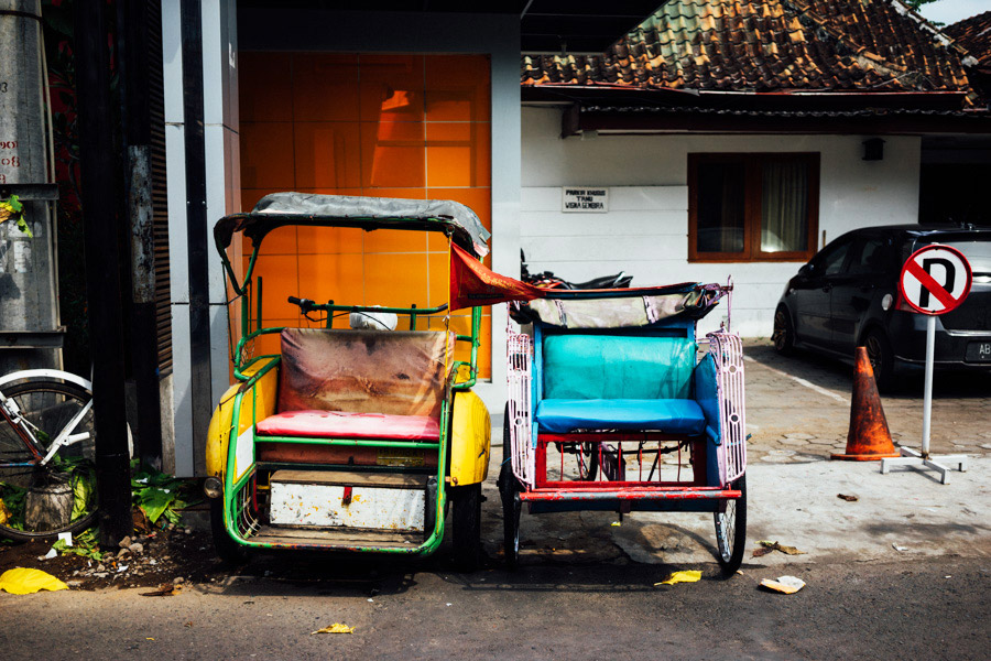Colorful tuk-tuks line the streets as their drivers take their midday siestas.