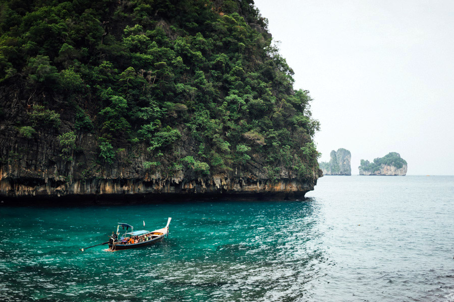 A perfectly domed limestone rock with the ocean slowly carving away its base, and a long-tail boat in the emerald waters of the Phi Phi Islands, just waiting for their photo to be taken.