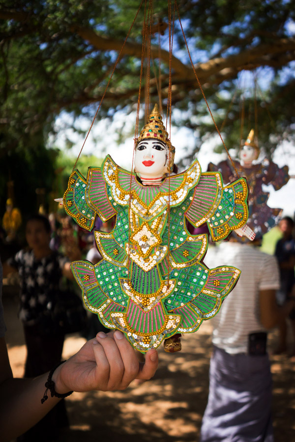 One of many decorative Burmese marionettes hanging from a tree outside one of the temples.