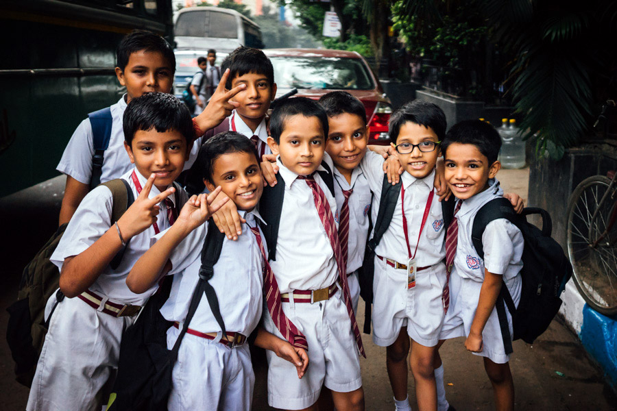 "On their way to a field trip just before boarding the bus, these boys spotted Alex and started giggling. ""Where are you from? What country??"" We realized then that we had not seen any other tourists in Kolkata."