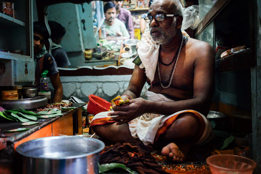 "The paan man (""paanwala"") putting a blend of areca nut, tobacco, and spices into a betel leaf. Sweet preparations of this triangular packet, which is meant to be chewed and then swallowed or spat out, have coconut powder, fennel seeds, cardamom, and more."