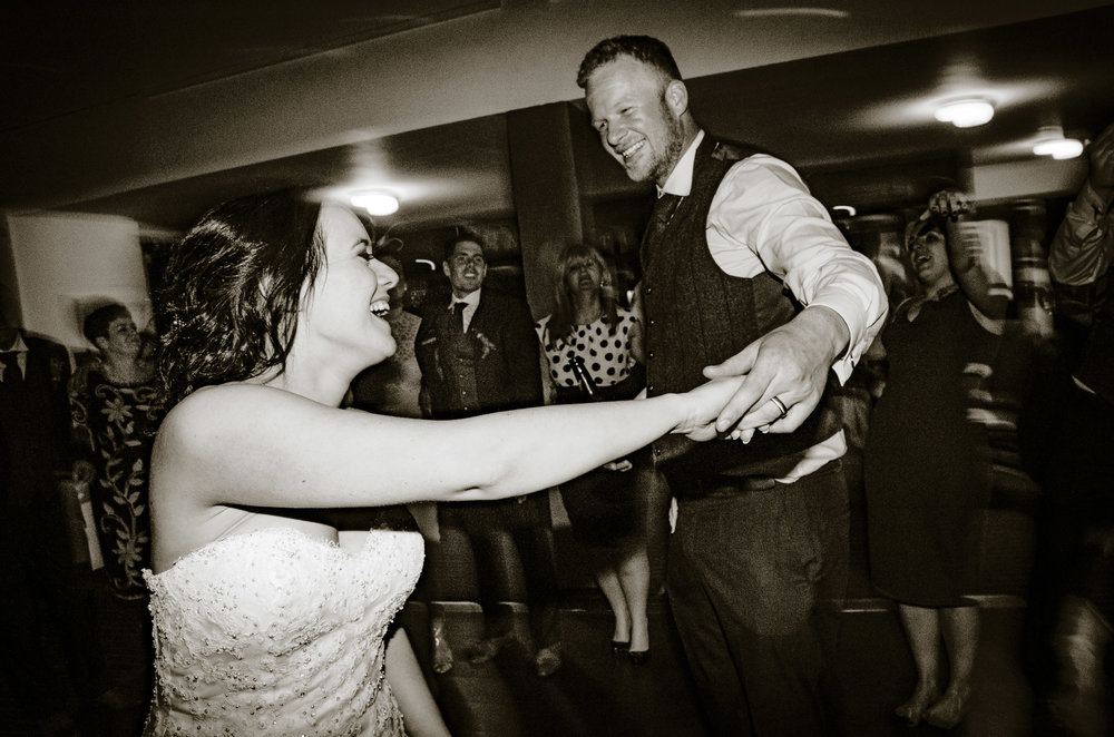 B+W. Candid. Close up. Two Shot. Bride and Groom dancing in center of the dancefloor encircled by friends and family.