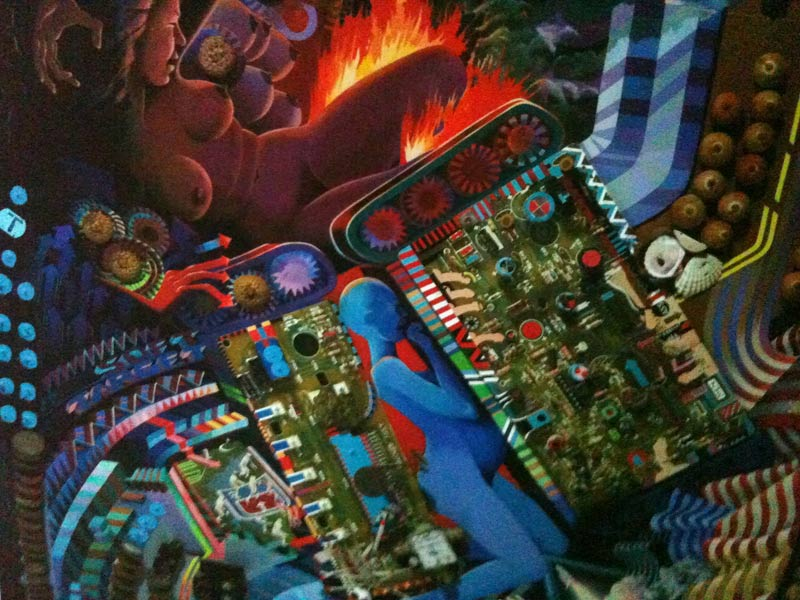 'War Machines: Conflagration Between Acorns and Monetary Units' Excerpt from construction made of acrylic on pizza box, canvas, constructions, phone parts, deadly nightshade seeds etc