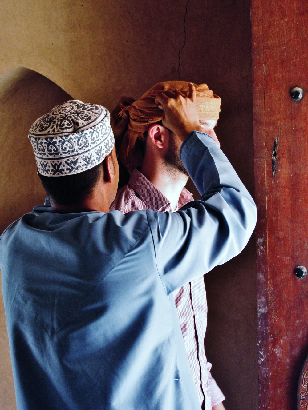 An Omani helps tie a  mussar,  or traditional Omani turban, on a student (Photo: CJ Aragon)