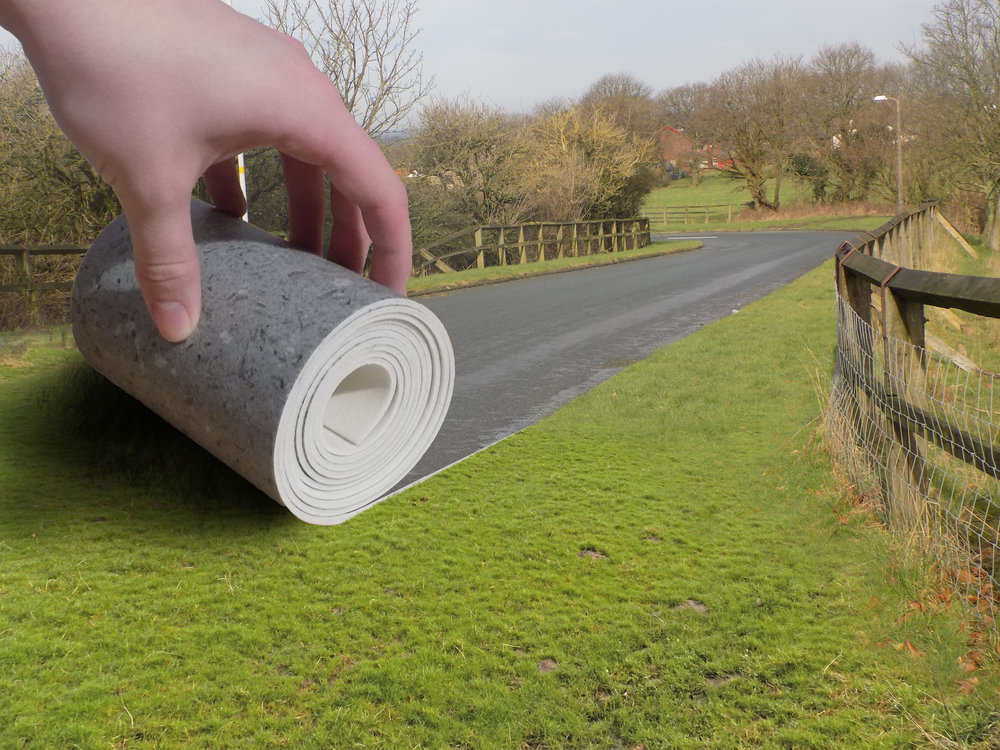 A hand rolling a carpet of road on the grass complete.jpg