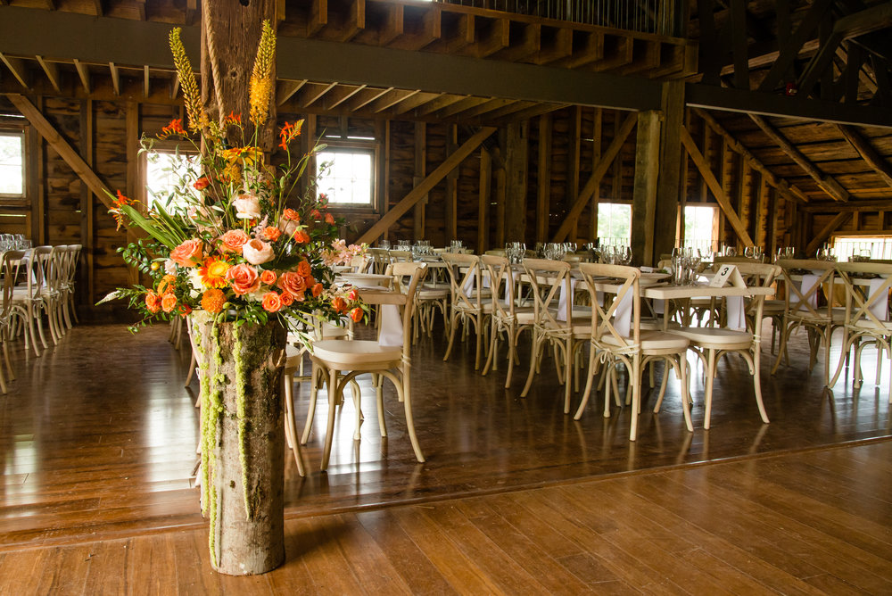 Orange, yellow and gold flowers decorate the barn
