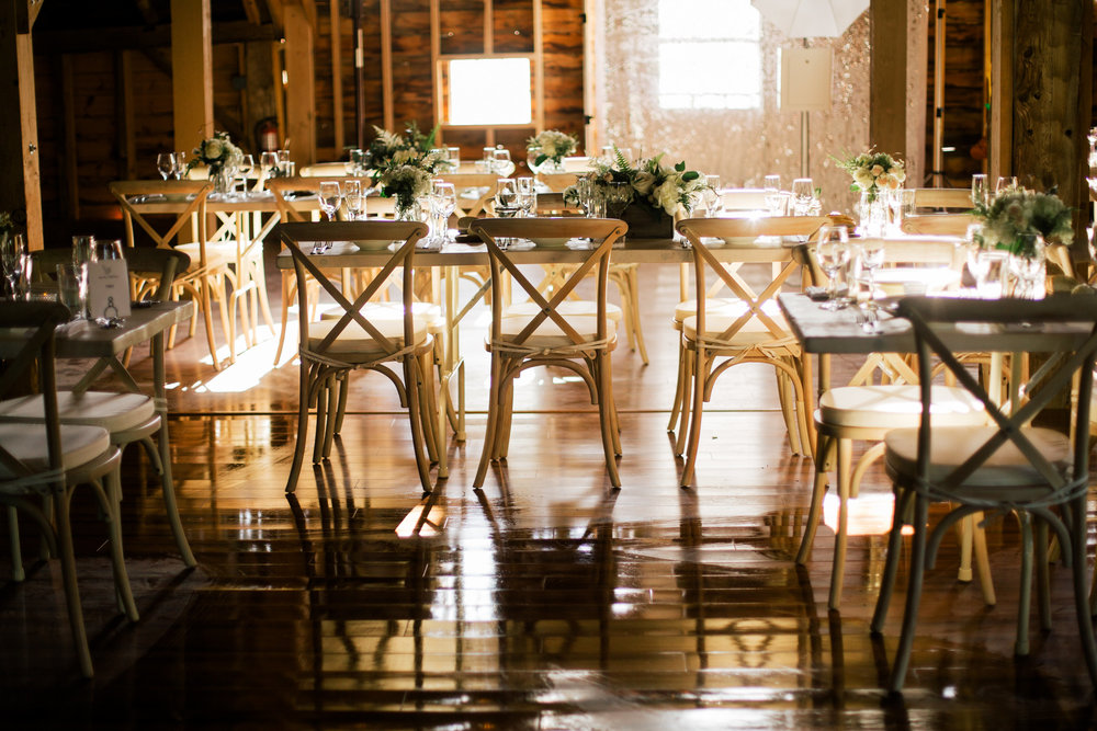 Sun sets through the many barn windows at the start of reception