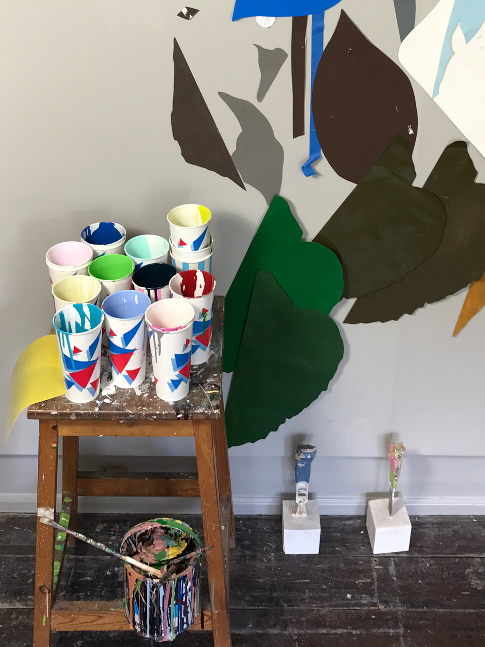 Gary Hume: Artist's stool, collection of waxed cups containing high gloss household paint, paper stencils, old tin of discarded high gloss paint, used painting spatulas set in plaster.