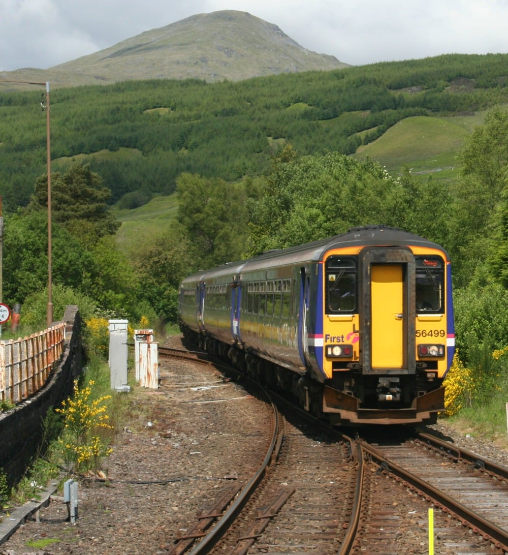 Fort William-bound rail service leaves Crianlarich. The Oban services go off to the left, beyond the white boxes/posts in this picture.