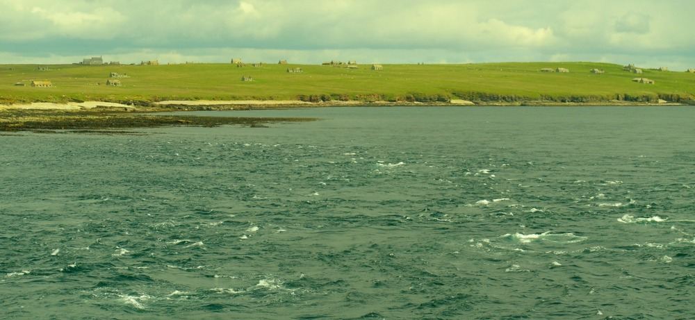 The deserted houses on the island of Stroma in the Pentland Firth, as well as the tide-race off its southern tip. This is a calm day.