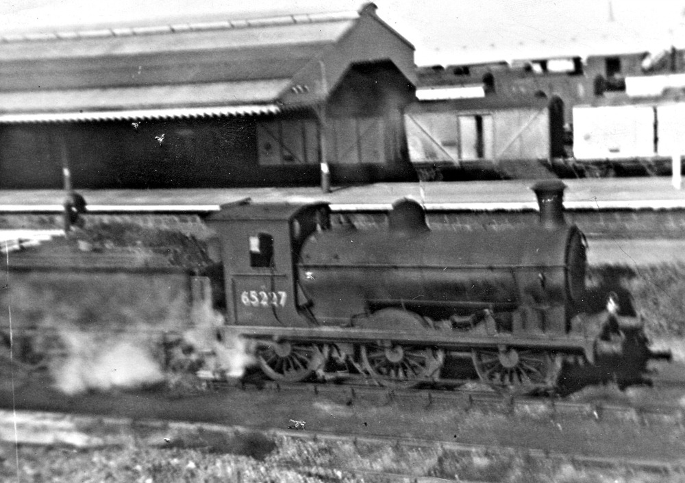 Class J36 65227 at Fraserburgh c.1960, outside the engine shed. 'Blue Spot' fish vans in background