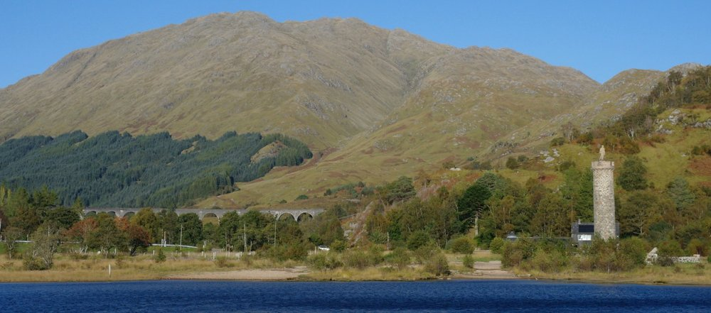 The Glenfinnan Monument (on the right) from Loch Shiel. The figure on top is just a generic Highlander, rather than a statue of Charlie. More interesting for many visitors is the Glenfinnan Railway Viaduct, seen in the background.