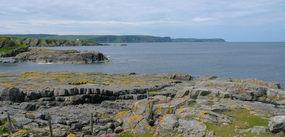 'The West Rocks.' This off-the-beaten-track stretch of coast on a calm summer day. Note Quarry Head with white hut - once an observation place for the former RAF bombing range that was located very near the Bonaventure wreck site.