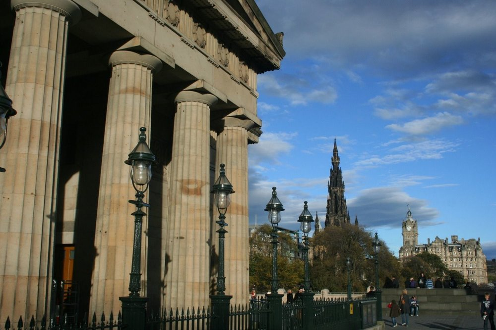 The fine neo-classical facade of the Royal Scottish Academy, Edinburgh, moments from Princes Street. The Scott Monument spire and the Balmoral Hotel (right) are further back.