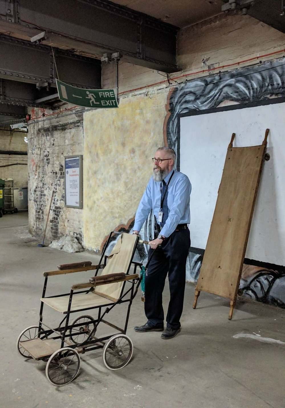 A World War I vintage wheelchair. Found in a store that had not been opened for years. Behind our guide, a stretcher of the same vintage. Before the decision not to repatriate bodies, the corpses of soldiers were taken home on these stretchers and left on the platform for relatives to identify.