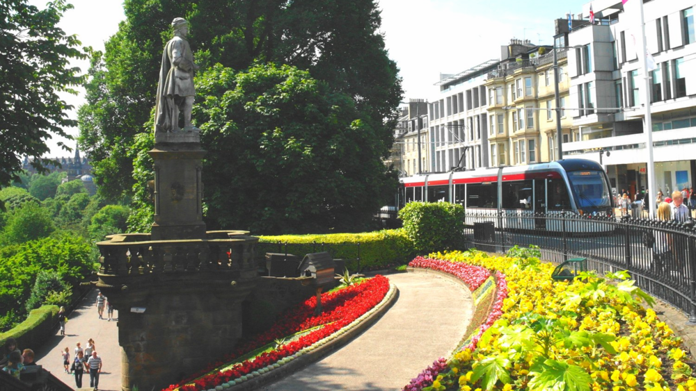 The poet Allan Ramsay's statue looks out from Edinburgh's Princes Street Gardens on the tram service that links city centre and airport.