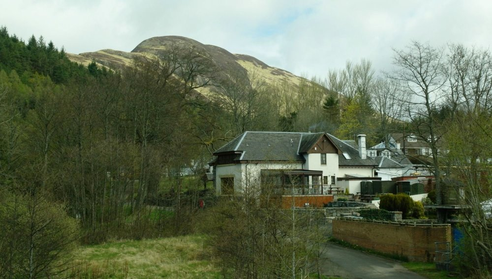 Conic Hill is on the skyline behind the village of Balmaha. It gives great views over the Loch Lomond islands. The Oak Tree Inn (back view!) is in the foreground. It also has its own micro-brewery. The road, bottom right, runs down to the Balmaha boatyard, from where you can hop over to the island of Inchcailloch.