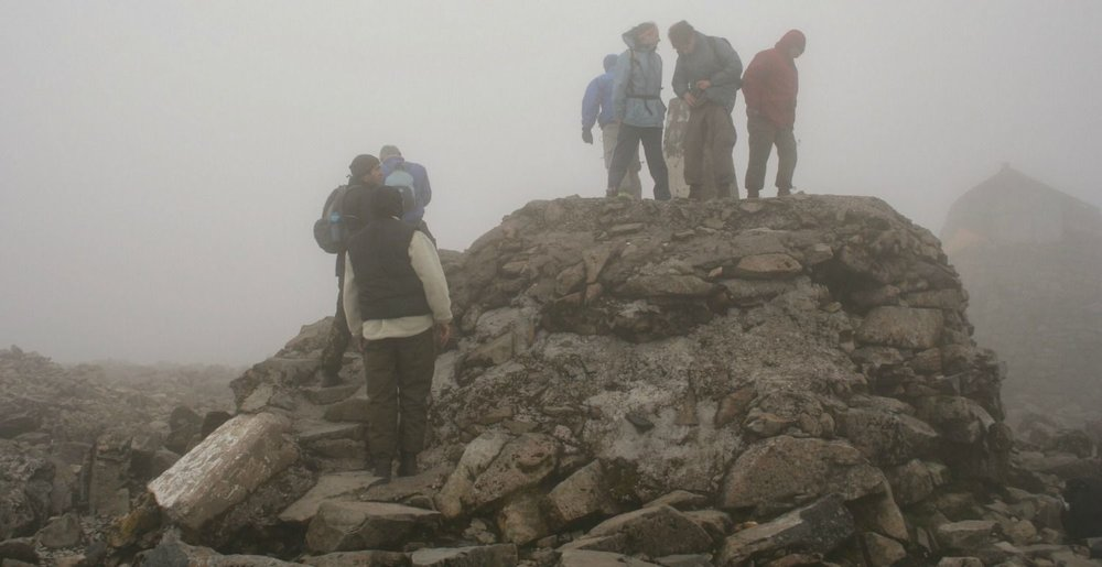 A summer day on the summit of Ben Nevis and they are queuing to stand on the summit cairn.
