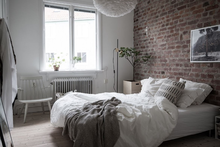 Exposed brick walls seem to calm rooms down. Perfect in a bedroom. Add some strong graphic details to add the modern touch.