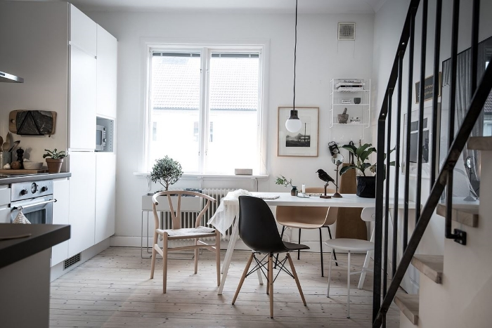 A few natural wood items and some greens bring life and warmth to this otherwise pretty stark room. Also, notice all the chairs are different styles which makes the room much more relaxed.