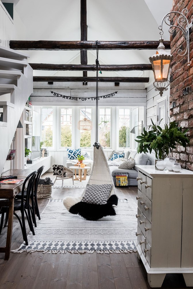 Exposed ceiling beams made useful with a hanging chair swing in the middle of the room.