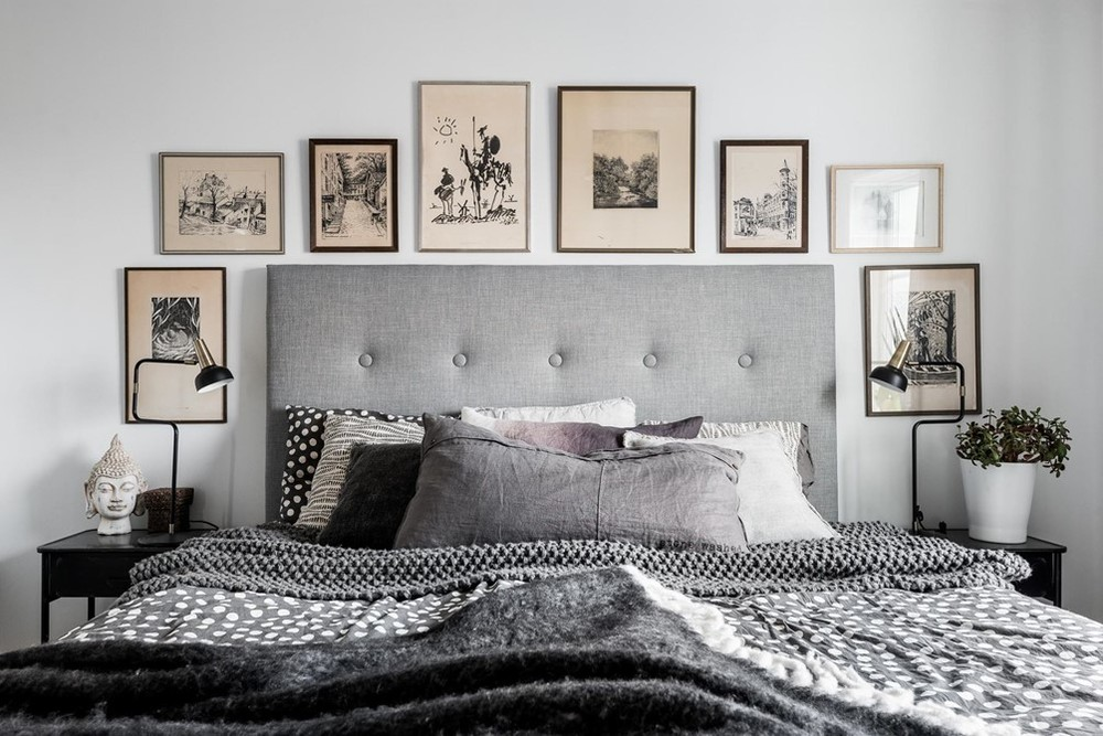 Master bedroom in peaceful grey hues. The aged black and white art prints lend a graphic yet warm quality.