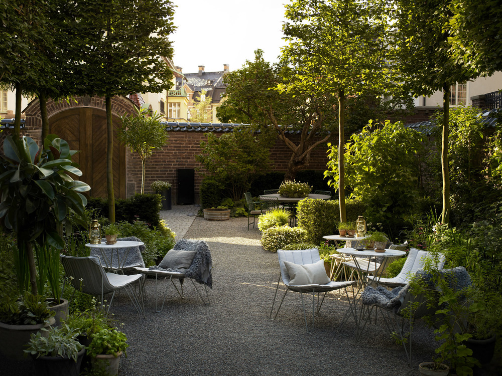 Lush garden surrounded by brick walls makes this hotel yard shielded from the buzzing city outside.