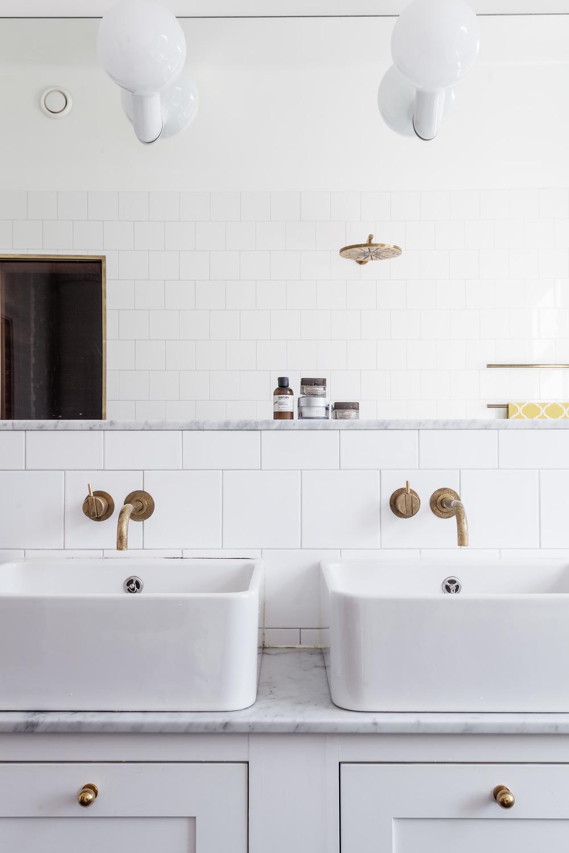 Brass details in a white bathroom.