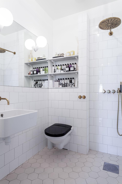 Tiled in shelves in a white bathroom.