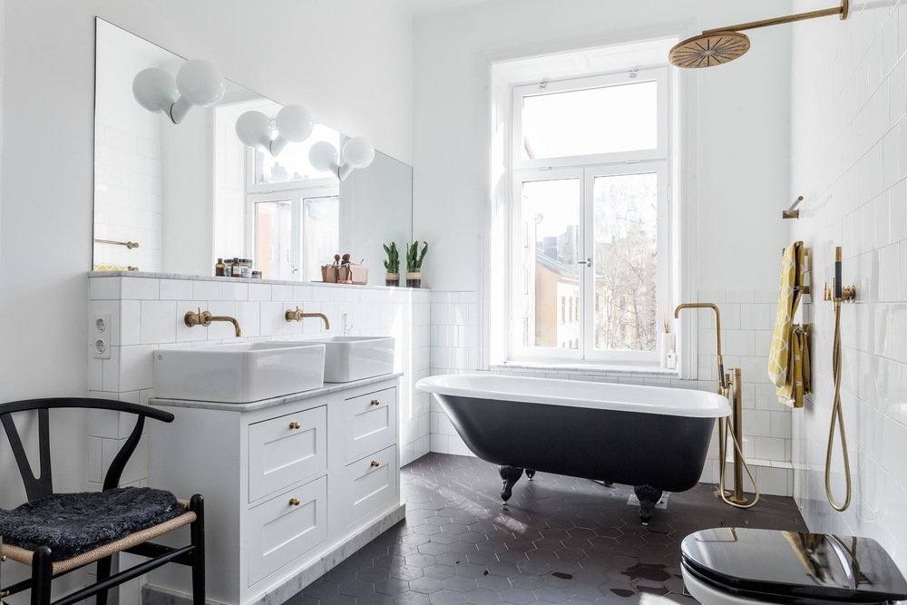 Beautiful black, white and marble bathroom with brass hardware.