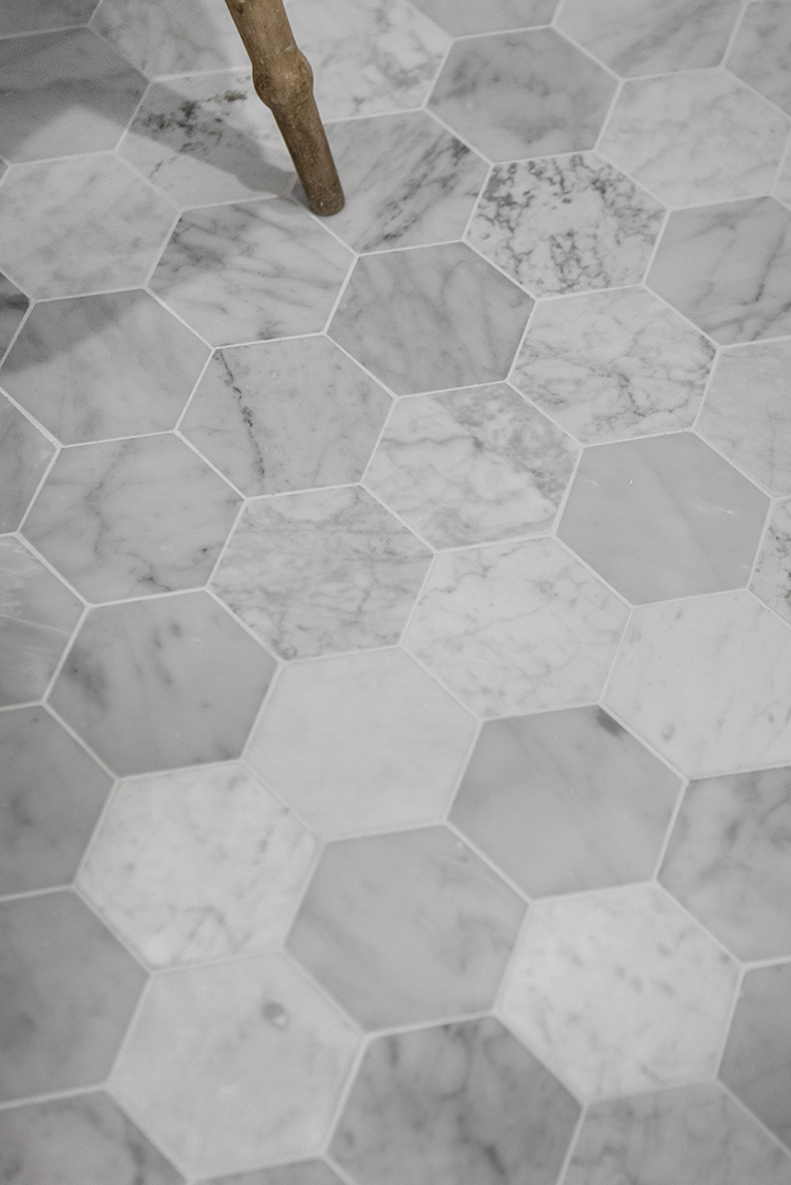 Hexagon marble tiles in a white bathroom.