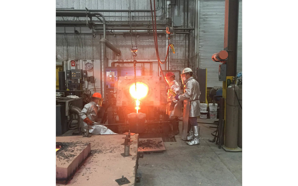 Then the molten bronze is transferred from the furnace to a poring vessel