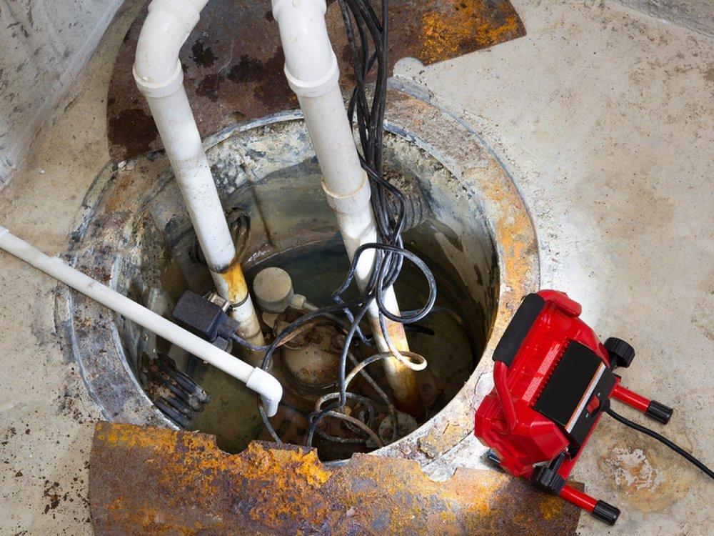 Repairing-A-Sump-Pump-In-A-Bas-55829624.jpg