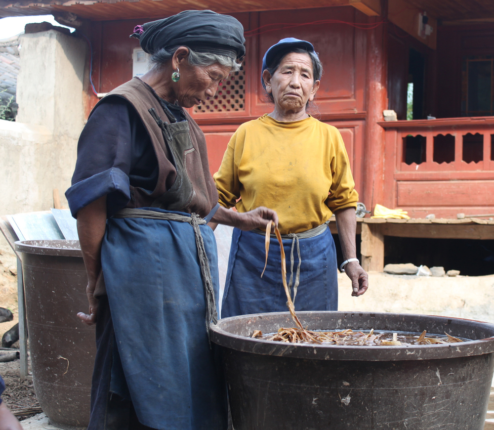 Naxi women wearing typical blue aprons and blue cap or coif.
