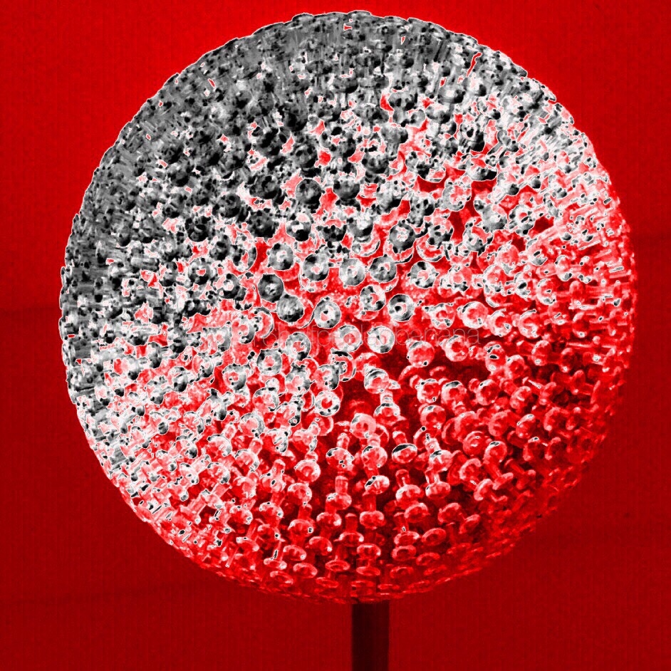 """black silver and red photo of a 7"""" flower made of push pins"""