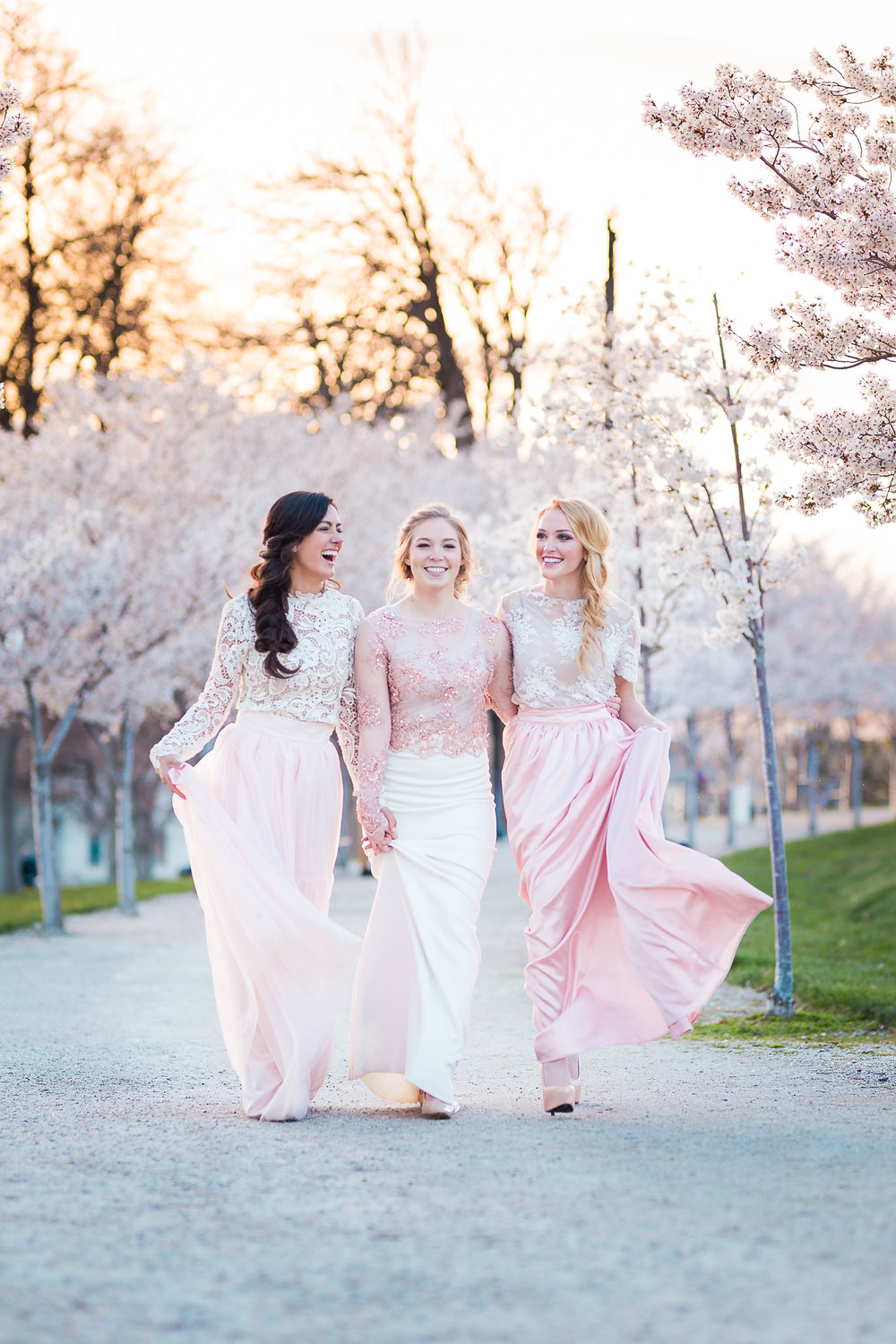 Three Brides Walk Under Blossoms