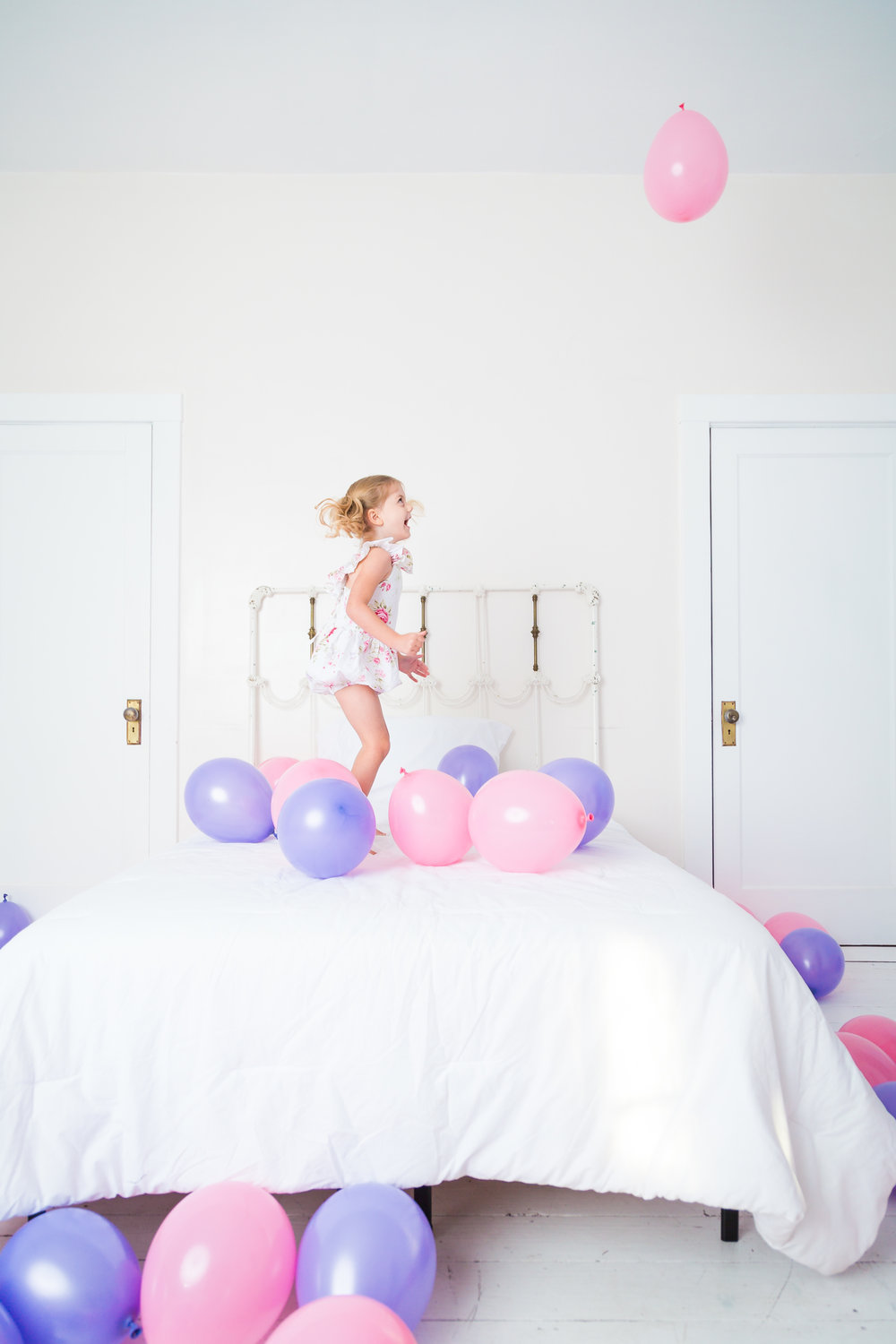 Girl Jumps on Bed Surrounded by Balloons