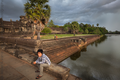 Afternoon thunderstorm anounces itself by creating a dramatic dark sky above Angkor Wat temple compound, as a visitor is waiting near the entrance, Siem Reap, Cambodia.