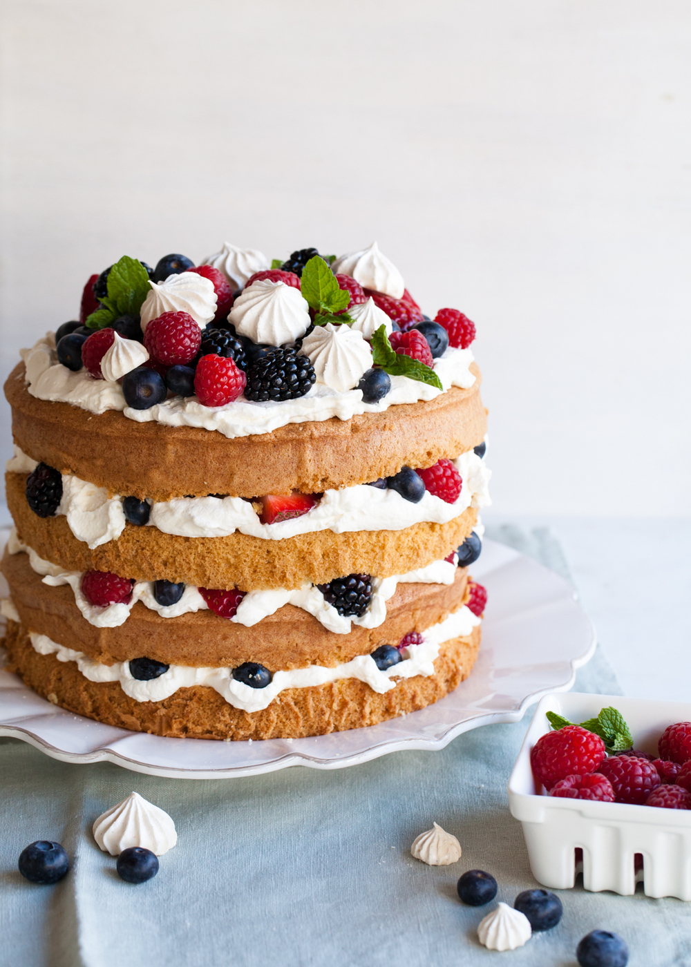 Eton Mess Cake with layers of sponge cake, sweetened whipped cream, crispy meringue, and fresh berries.